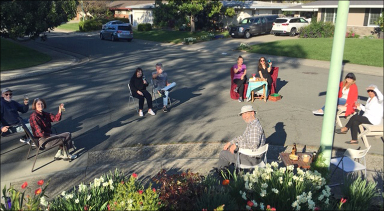 A photo of a group of neighbors getting together  in the street with all their chairs carefully placed 6' apart.