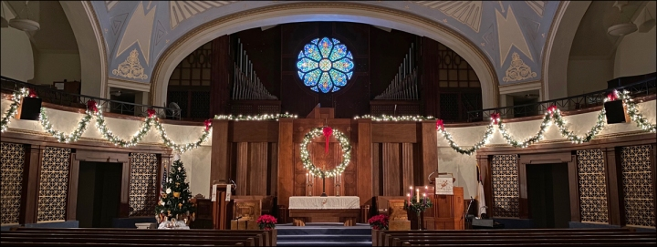 A picture of the sanctuary at Christmas time with lighted garlands along the balcony.